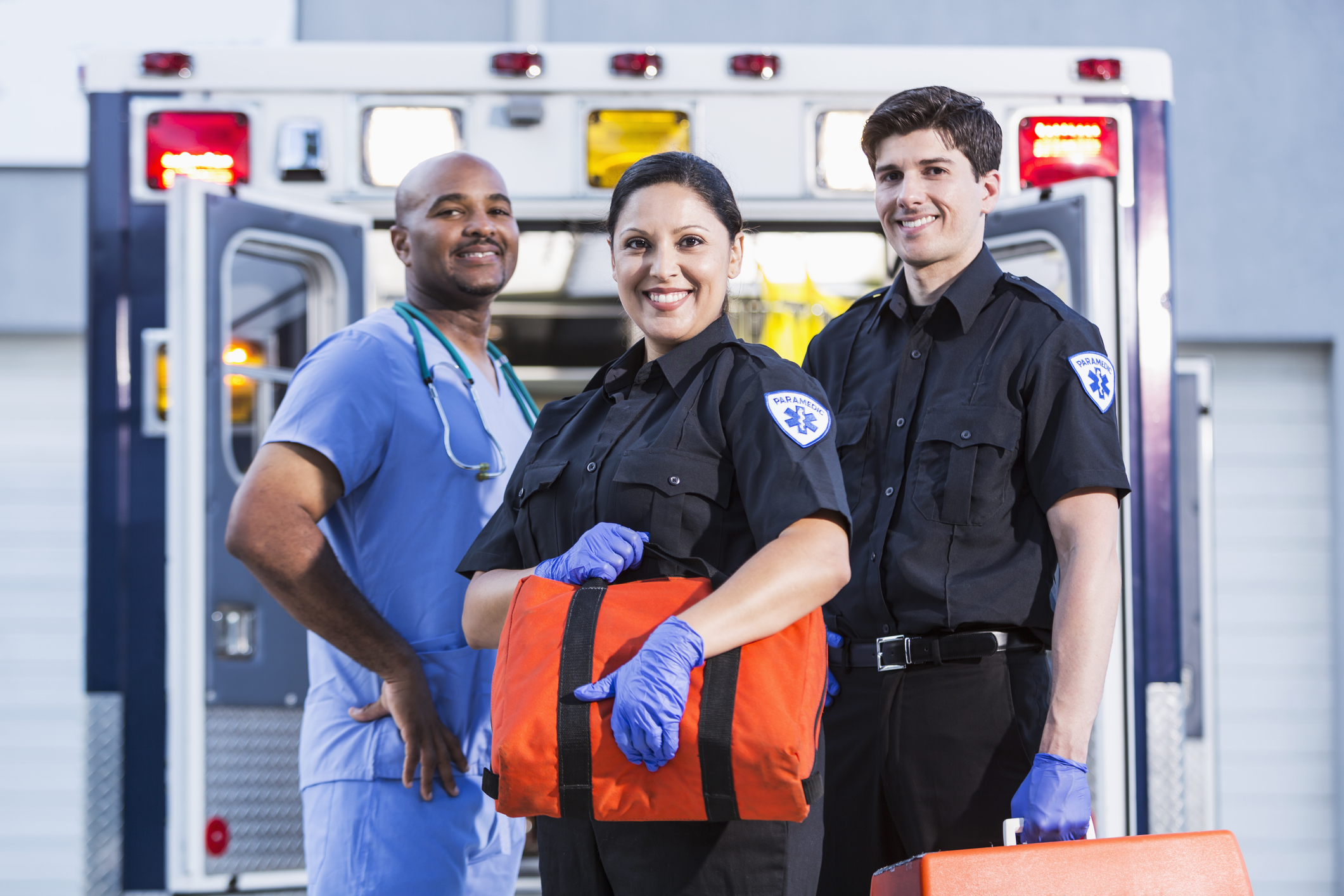 Paramedics and doctor standing at rear of ambulance.  Focus on paramedics (30s, Hispanic).